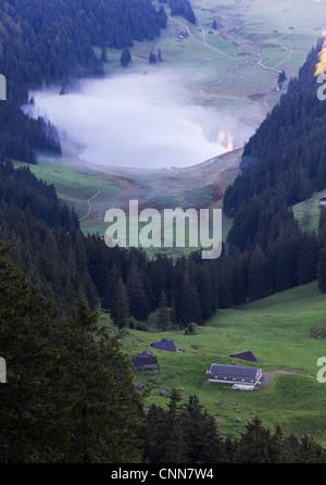 Tal mit See und Nebel schweben und Mountain peaks reflektierenden umgeben von hohen, steilen, felsigen Berg Wände - Stockfoto
