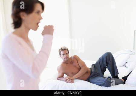 Mann beobachtet Frau ihre Zähne putzen - Stockfoto