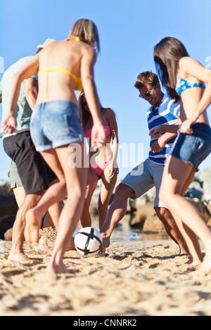 Freunden Fußball spielen am Strand - Stockfoto