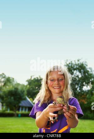 Mädchen halten Frosch im Hinterhof - Stockfoto