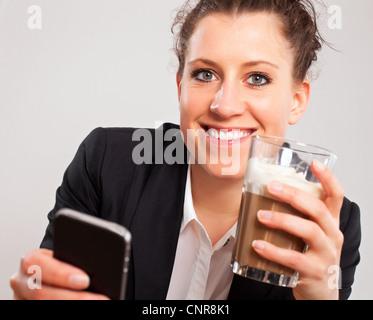 Closeup Portrait eines Büro-Mädchen mit einem Telefon und Kaffee in der hand genießen Sie ihre Pause - Stockfoto