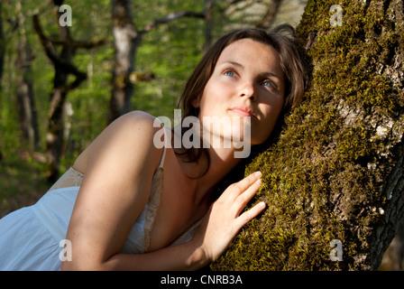 Schöne junge Frau gegen eine weiche ruht tief im Wald Baum - Stockfoto