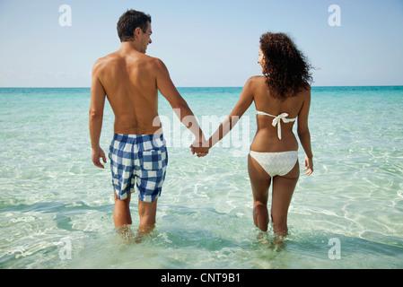 Paar Hand in Hand beim Waten im Meer, Rückansicht - Stockfoto