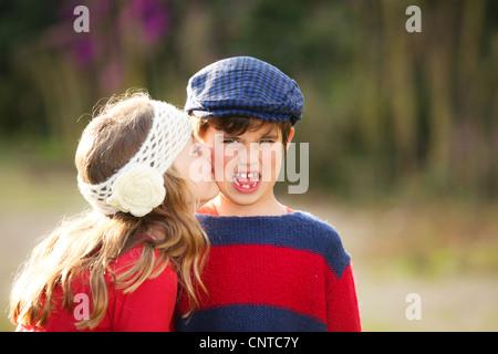 kleines Mädchen peinlich junge Kuss geben. - Stockfoto
