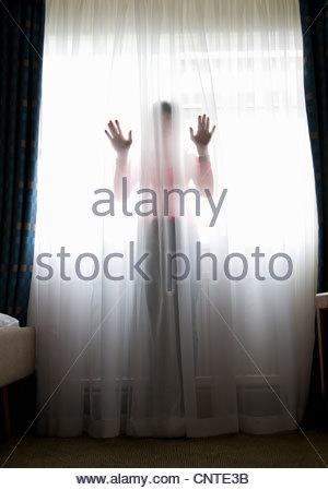 Frau stehend hinter schiere Vorhang - Stockfoto