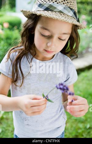 Mädchen untersuchen Blume im freien - Stockfoto