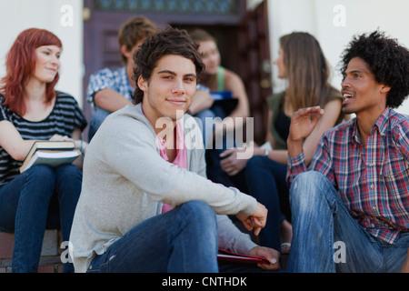 Studenten sitzen zusammen auf dem campus - Stockfoto