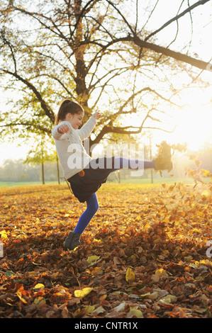Lächelndes Mädchen spielen im Herbst Blätter - Stockfoto