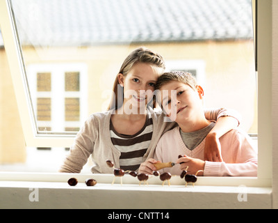 Kinder, die zusammen im Fenster stehen - Stockfoto