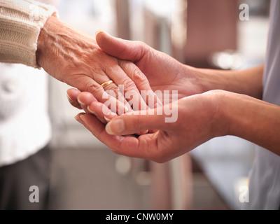 Krankenschwester mit älteren mans hand - Stockfoto