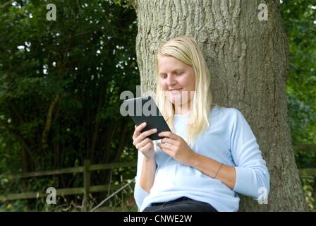 Blonde Mädchen liest einen Amazon Kindle elektronische e-Reader im Freien an einen Baum Hayley Williamson Herr gelehnt - Stockfoto