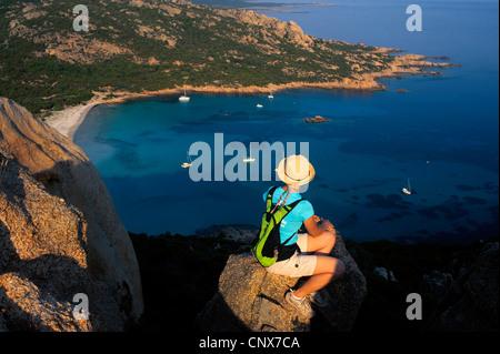 weibliche Wanderer sittin auf einem Felsen über der Bucht von Roccapina, Frankreich, Korsika - Stockfoto