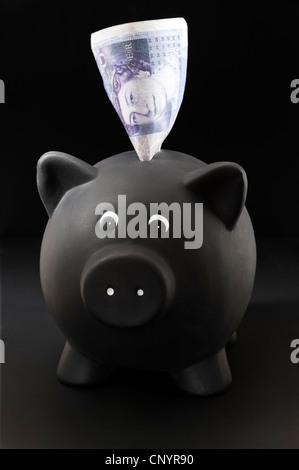 Schwarz Sparschwein mit £20 Hinweis aus der Spitze. auf schwarzem Hintergrund - Stockfoto