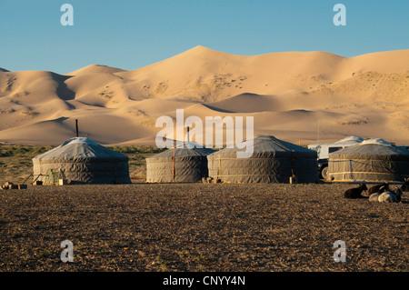 nomadische Gers unter den Sanddünen von Khongoryn Els bei Sonnenuntergang in der Wüste Gobi in der Mongolei - Stockfoto