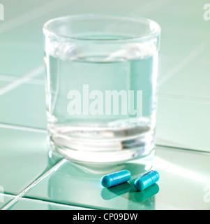 Blaue Pillen und ein Glas Wasser auf Aqua Fliesen-Oberfläche - Stockfoto