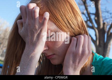 In der Nähe von einem 16 Jahre alten Mädchen erleben Angst und bedeckte ihr Gesicht mit den Händen im Freien. - Stockfoto