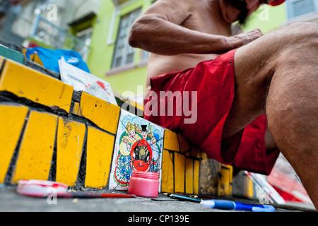Jorge Selarón malt ein Bild vor seinem Haus auf Selaron Treppe (Escadaria Selarón) in Rio De Janeiro, Brasilien. - Stockfoto