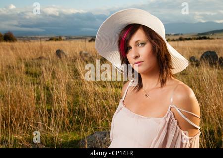 Junge Frau sitzt in einem Feld - Stockfoto