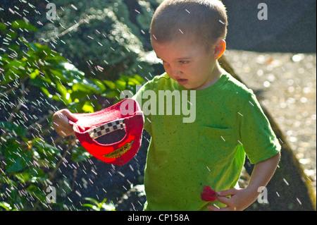 4 Jahre alten autistischen jungen fangen Wasser aus Sprinkleranlagen in Hut. - Stockfoto