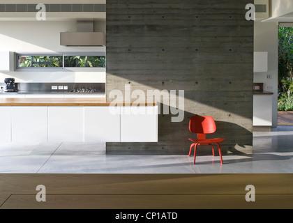 Roten geformten Stuhl gegen die Betonwand im Haus Weinstein Vaadia Architekten, Hofit, Israel. HOFIT Haus, Israel - Stockfoto