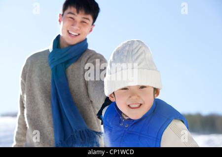 Vater mit Sohn im Schnee spielen - Stockfoto