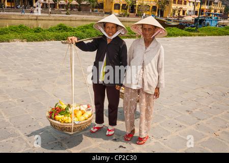 Zwei vietnamesische Frauen, eine tragen Früchte, Hoi An, Provinz Quang Nam, Vietnam - Stockfoto