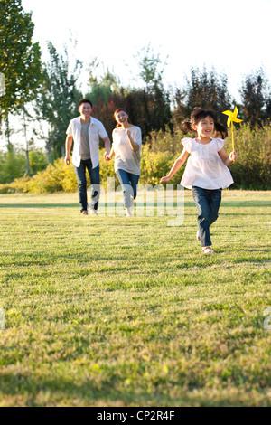 Junge Chinesin, die in einem Feld mit einem Windrad mit ihrer Familie spielen - Stockfoto