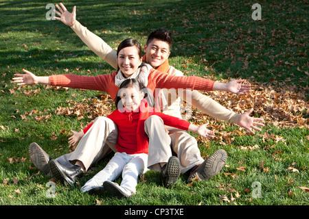 Junge Familie Spaß mit Arme ausgestreckt auf dem Rasen sitzen - Stockfoto