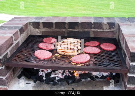 ... Burger Und Würstchen Kochen Auf Einen Backstein Grill   Stockfoto