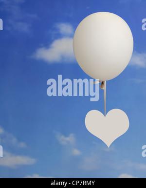 weißes Herzform hängend auf einem weißen Ballon vor blauem Himmel mit Wolken - Stockfoto