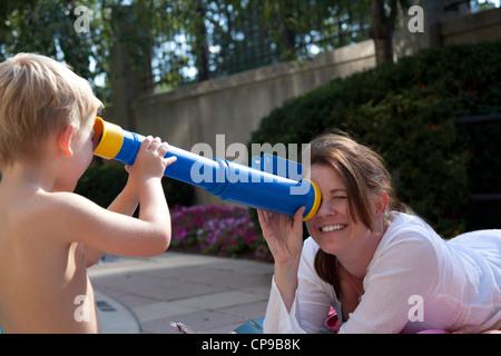 Mutter und Sohn spielt mit Spielzeug-Teleskop in der Nähe von Pool - Stockfoto