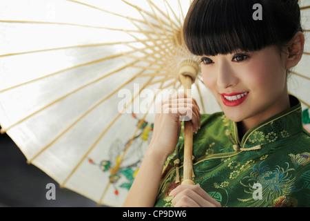 Junge Frau trägt einen traditionellen chinesische Kleidung und einen Regenschirm hält - Stockfoto