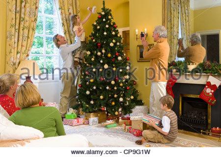 Familie von Weihnachtsbaum, Großvater nehmen Foto von Mädchen (5-7) Putten Engel Dekoration auf Baum - Stockfoto