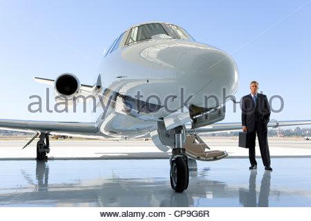 Pilot mit dem Aktenkoffer mit dem Flugzeug auf der Piste - Stockfoto
