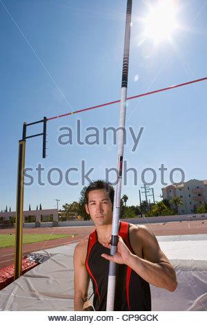 Junge männliche Stabhochsprung Athlet mit Pol von bar, Porträt (Sonne Flare) - Stockfoto