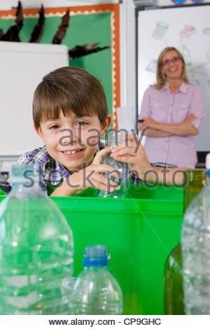 Lächelnd Schüler setzen Glas in Papierkorb - Stockfoto