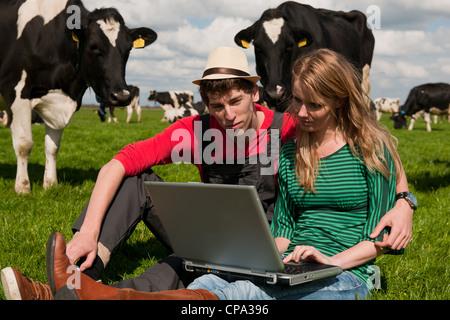 Junges Paar Bauern in Feld-Hof mit Laptop und schwarze und weiße Kühe - Stockfoto