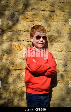 8 Jahre alter Junge an eine Wand gelehnt. - Stockfoto
