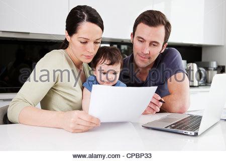 Ein paar und ihr Baby Sohn betrachten ihre Haushaltsfinanzen - Stockfoto
