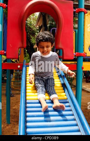 Indian 3 jährige eine Rutsche hinunter - Stockfoto