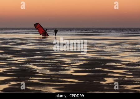 Zwei Männer am Strand bei Sonnenuntergang Spaziergang mit einem Kite Surfer, Essaouira, Marokko - Stockfoto