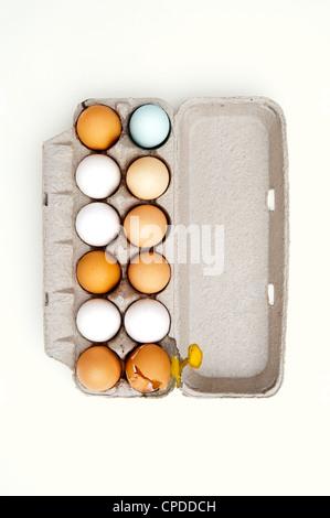 Gefärbten Eiern und einem gebrochenen Ei im Karton