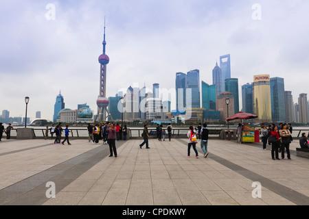 Fußgänger und Touristen auf den Bund, die futuristische Skyline von Pudong über den Huangpu-Fluss über Shanghai, - Stockfoto