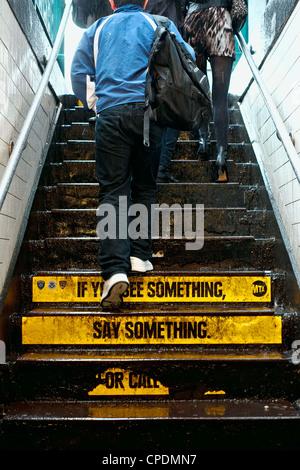 """Menschen verlassen New Yorker u-Bahnstation in Regen mit """"Wenn Sie etwas sagen, etwas"""" Warnung auf Treppe - Stockfoto"""