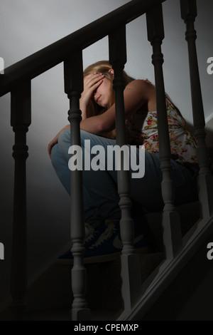 Junge Mädchen sitzen auf dunklen Treppen wieder anzeigen - Stockfoto