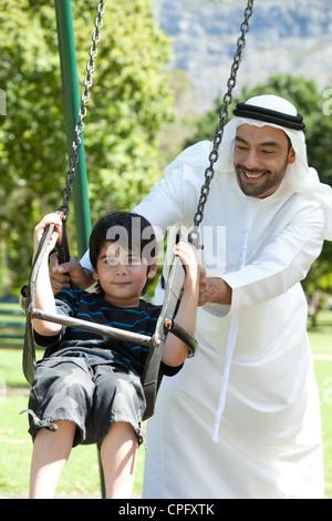 Junge auf Schaukel, gedrängt von seinem arabischen Vater lächelnd sitzt. - Stockfoto
