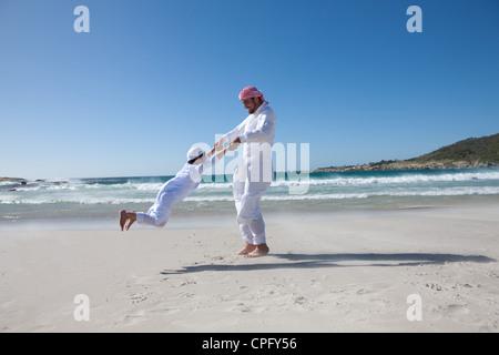 Arabische Vater seinen Sohn um am Strand zu spinnen. - Stockfoto