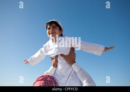 Arabische Vater heben seinen Sohn am Strand, junge erhobenen Armen. - Stockfoto