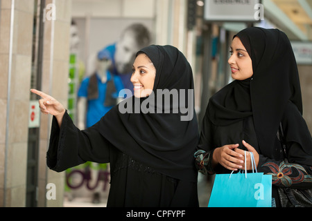Zwei arabische Frauen mit Einkaufstaschen in der Mall, Frau zeigt. - Stockfoto
