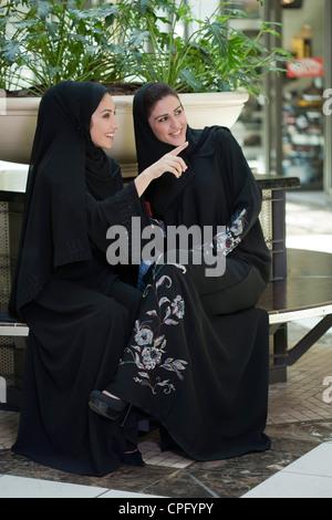 Zwei junge arabische Frauen sitzen in der Mall, Frau zeigt. - Stockfoto